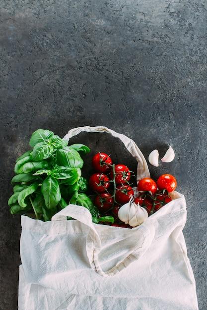 Sac réutilisable avec épicerie. sac fourre-tout, gaspillage minimal. basilic frais, tomates cerises, ail dans un sac en tissu Photo Premium