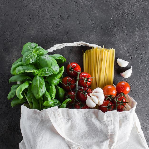 Sac réutilisable avec épicerie. sac fourre-tout, gaspillage minimal. basilic, tomates cerises, ail dans un sac en tissu Photo Premium