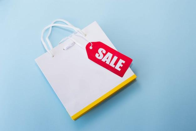 Sac shopping blanc avec une étiquette rouge en vente sur le bleu. espace de copie Photo Premium