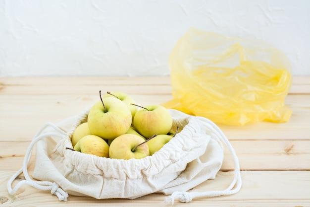 Sac en toile avec des liens avec des pommes et un sac en plastique sur un fond en bois naturel Photo Premium