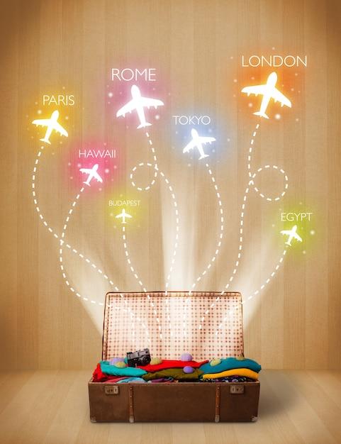 Sac de voyage avec des vêtements et des avions colorés envolant sur fond grungy Photo Premium