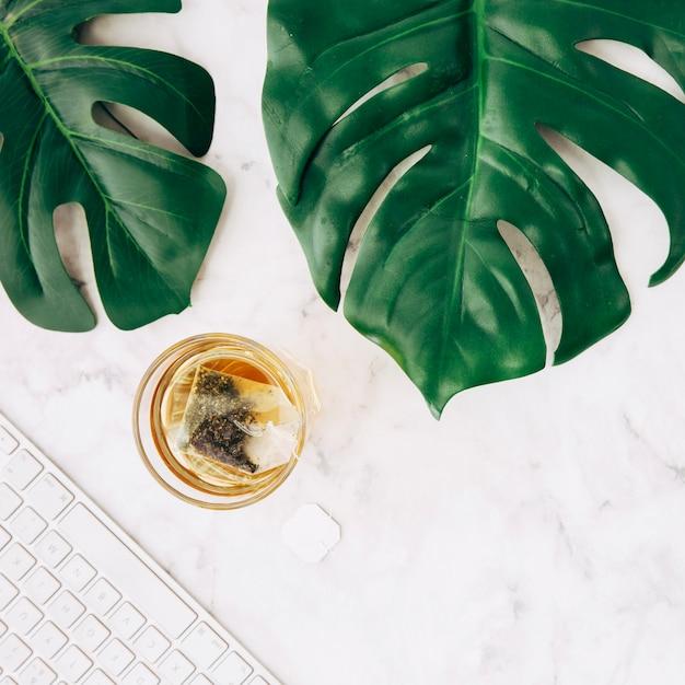 Sachet de thé dans une tasse en verre transparent; feuilles de monstera vert et clavier sur fond texturé en marbre blanc Photo gratuit