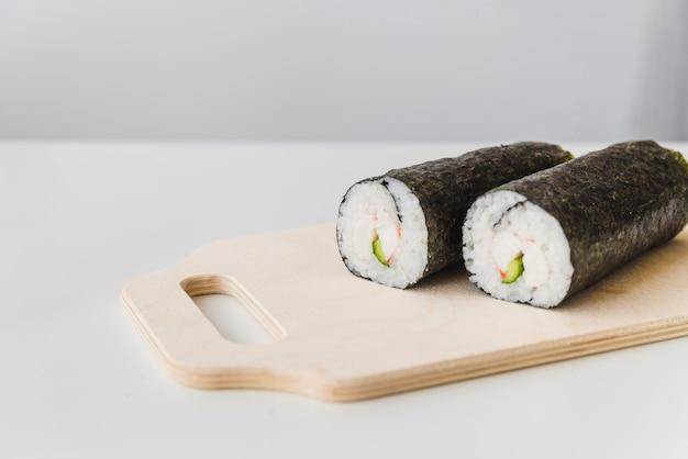 Sachets de sushi sur planche à découper Photo gratuit