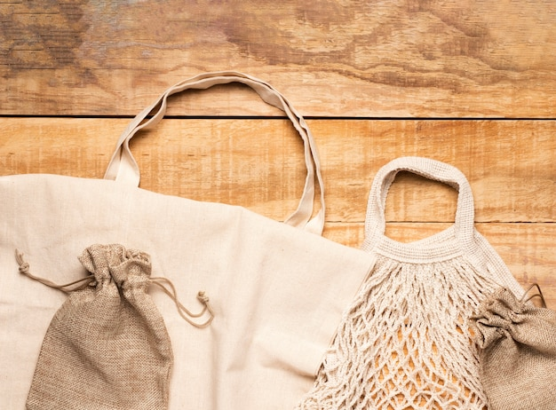 Sacs écologiques blancs sur fond en bois Photo gratuit