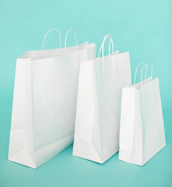 Sacs en papier blanc sur fond bleu Photo gratuit