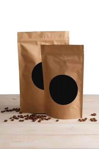 Sacs en papier kraft avec café sur une table en bois Photo Premium