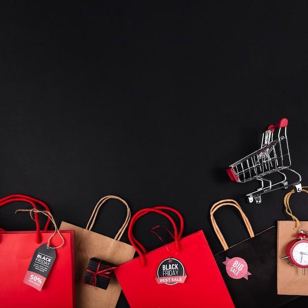 Sacs de shopping de différentes couleurs avec panier Photo gratuit