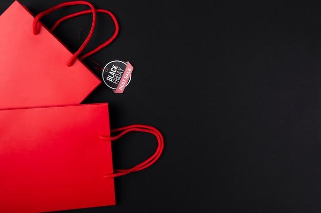 Sacs shopping rouges avec autocollant de vendredi noir Photo gratuit