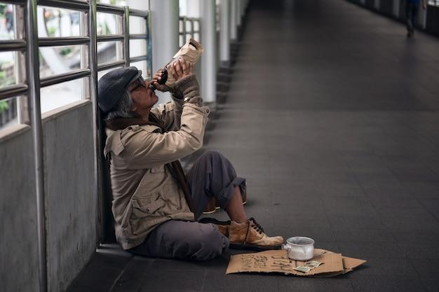 Sad vieil homme sans-abri boire de la bière Photo Premium