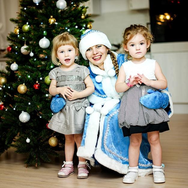 Saint-pétersbourg, Russie - 24 Décembre 2016: Voeux Du Nouvel An Des Enfants. Enfants Jouant Avec La Jeune Fille Des Neiges. Salutations, Cadeaux, Dansez Autour D'un Sapin De Noël. Portraits De Famille. Photo Premium