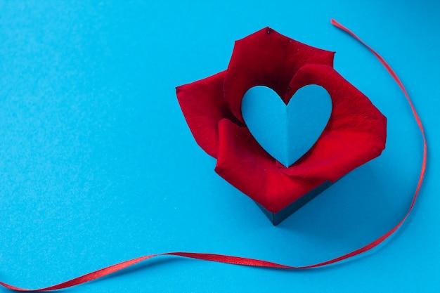 Saint valentin et le 8 mars, pétales de rose et coeur en boîte sur fond bleu Photo Premium