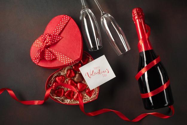 Saint valentin avec une boîte de chocolats en forme de coeur avec une bouteille de champagne avec des verres et une note Photo Premium