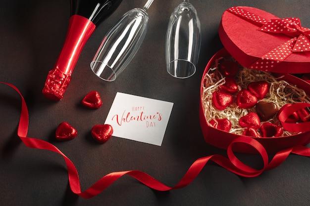 Saint valentin avec une boîte de chocolats en forme de coeur avec une bouteille de vin mousseux avec des verres et une note Photo Premium