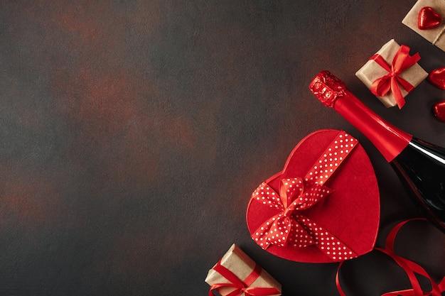 Saint valentin avec une boîte de chocolats sous forme de cadeaux sincères et de vin mousseux. vue de dessus avec espace de copie. Photo Premium