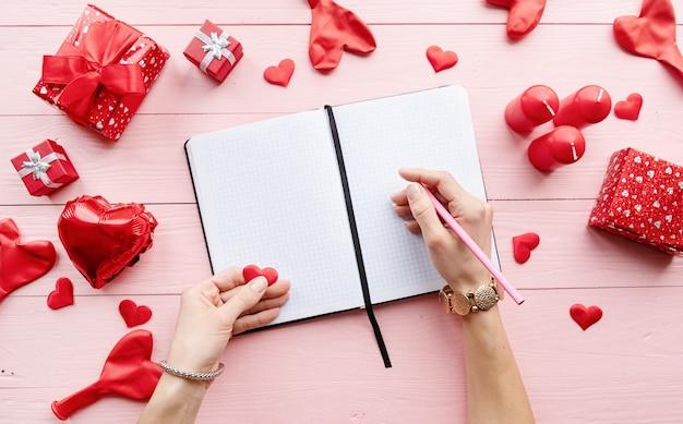 La Saint-valentin. Femme écrivant Sur Des Feuilles De Papier Vierge Sur Une Table En Bois Rose Décorée De Bougies Et De Cadeaux Valentine Rouge Photo Premium