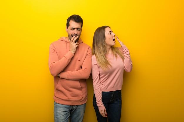 Saint valentin groupe de deux personnes sur fond jaune bâillant et couvrant la bouche grande ouverte avec la main Photo Premium