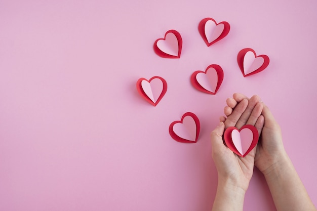 La Saint-valentin. Les Mains De La Femme Tiennent Coeur Sur Fond Rose Photo Premium
