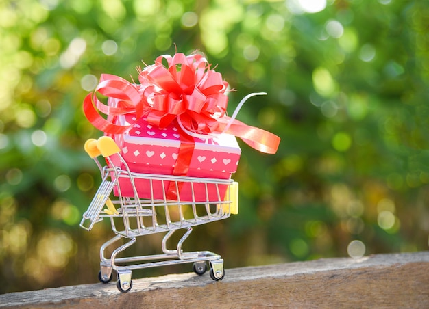 Saint valentin shopping et boîte cadeau présente boîte avec ruban rouge arc sur le panier achat en ligne de vacances Photo Premium