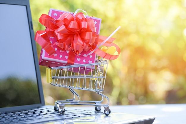 Saint valentin shopping et boîte de cadeau rose boîte présente avec ruban rouge arc sur le panier d'achat en ligne Photo Premium