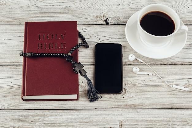 Sainte bible et smartphone avec une tasse de café noir Photo Premium