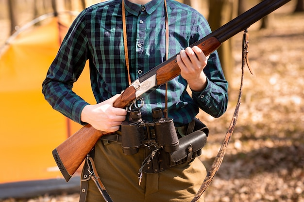 Saison de chasse d'automne. homme chasseur avec une arme à feu. chasse dans les bois Photo Premium
