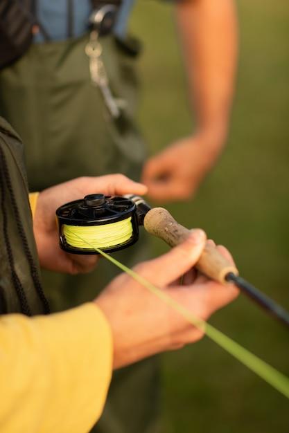 Saison de pêche. gros plan de la main du pêcheur avec rotation Photo Premium