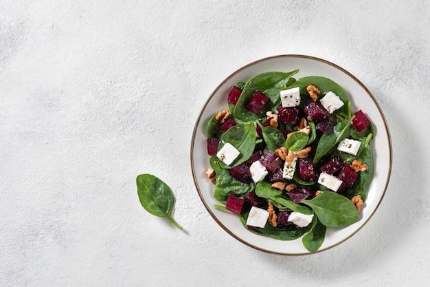 Salade de betteraves frites, d'épinards, de roquette, de fromage de chèvre doux et de noix dans une assiette légère. vue de dessus, espace de copie. Photo Premium