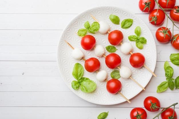 Salade caprese de tomates, fromage mozzarella et basilic sur une assiette blanche. cuisine italienne. espace de copie Photo Premium
