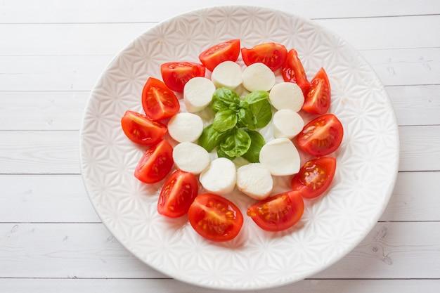 Salade caprese de tomates, fromage mozzarella et basilic sur une assiette blanche. cuisine italienne. Photo Premium