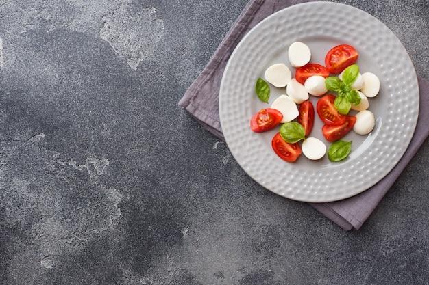Salade caprese de tomates, fromage mozzarella et basilic. cuisine italienne. espace de copie Photo Premium