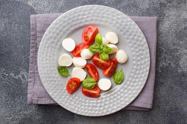 Salade caprese de tomates, fromage mozzarella et basilic. cuisine italienne. Photo Premium