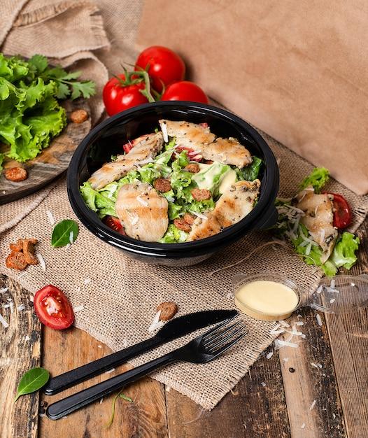 Salade césar au poulet avec parmesan haché, tomate, laitue, craquelins. Photo gratuit