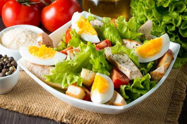 Salade césar dans un bol blanc sur une table en bois Photo Premium