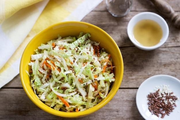 Salade De Chou De Chou, Carottes Et Diverses Herbes Avec De La Mayonnaise Dans Une Grande Assiette Sur Un Fond En Bois. Photo Premium