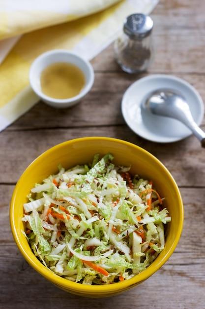 Salade De Chou De Chou, Carottes Et Diverses Herbes Avec De La Mayonnaise Dans Une Grande Assiette Sur Une Surface En Bois Photo Premium