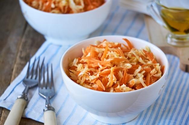 Salade De Chou Frais, Carottes Et Huile D'olive Dans Un Bol Blanc Sur Une Table En Bois Photo Premium