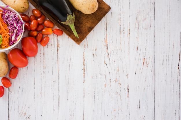 Salade de chou; tomates; pommes de terre et aubergines au coin d'une table blanche Photo gratuit