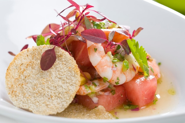 Salade de crevettes close-up avec la pastèque, décorée avec des fleurs comestibles. Photo Premium