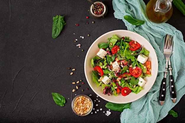 Salade diététique avec tomates, feta, laitue, épinards et pignons. Photo Premium