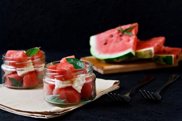 Salade d'été au melon d'eau, fromage blanc et basilic dans un bocal en verre sur fond noir Photo Premium