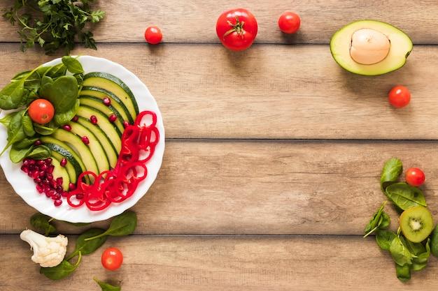 Salade de fruits et de légumes frais dans une assiette blanche sur une table en bois Photo gratuit