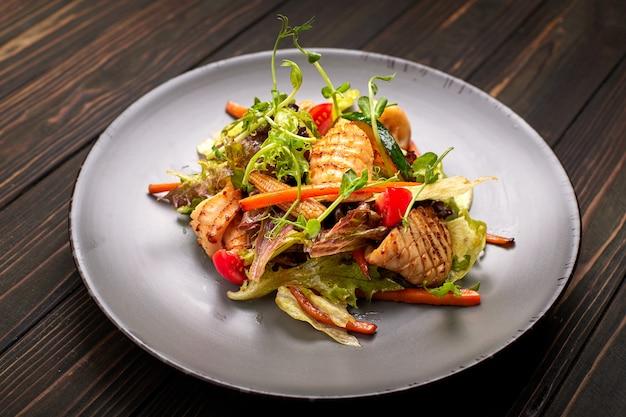 Salade De Fruits De Mer Avec Calamars Grillés, Maïs, Carottes, Tomates Et Laitue, Sur Une Plaque Grise, Sur Une Table En Bois Photo Premium