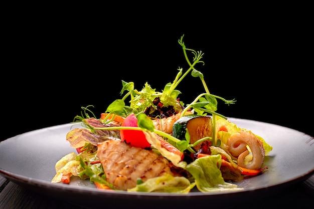 Salade De Fruits De Mer Avec Calamars Grillés, Maïs, Carottes, Tomates Et Laitue, Sur Une Plaque Grise Photo Premium