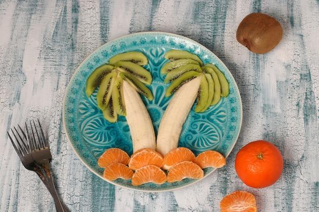 Salade de fruits saine pour les enfants de kiwi, bananes et mandarines en forme de palmier Photo Premium