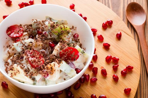 Salade de fruits en tranches de fruits, fourrés à la crème glacée et saupoudrés de chocolat Photo Premium