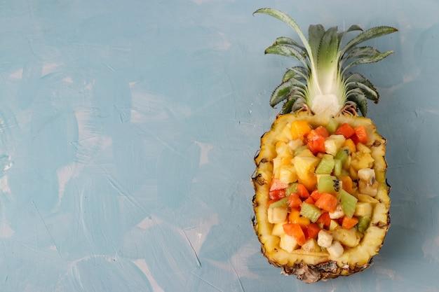 Salade De Fruits Tropicaux Dans La Moitié D'ananas Sur Fond Bleu Clair, Orientation Horizontale, Espace Copie, Vue De Dessus Photo Premium