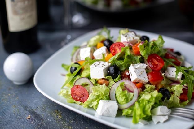 Salade De Grèce Olives Tranchées Vin Rouge à L'intérieur De La Plaque Blanche Photo gratuit