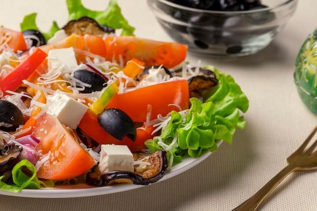 Salade grecque au fromage feta, à la tomate, à la laitue et aux olives noires séchées au soleil. Photo Premium