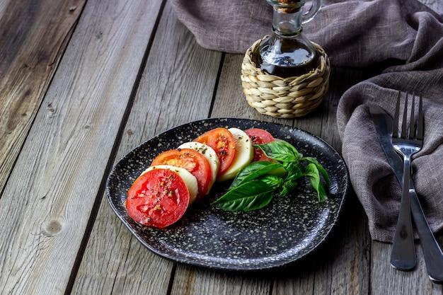 Salade italienne caprese avec mozzarella et tomates. en bois. la nourriture saine. Photo Premium