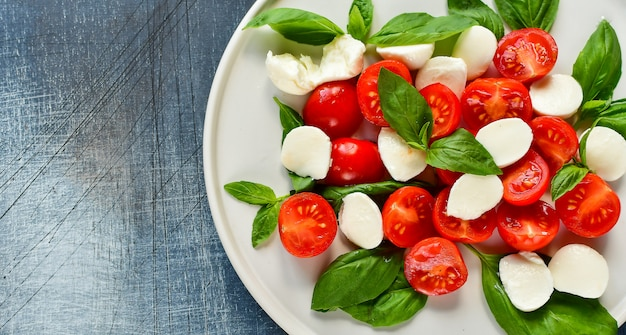 Salade italienne caprese: tomates rouges, mozzarella et basilic, cuisine italienne. déjeuner sain. Photo Premium